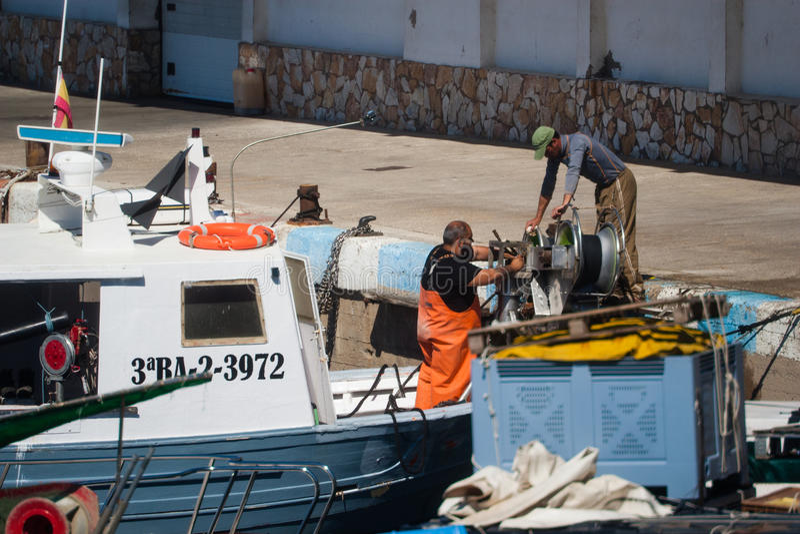 Palamos, Catalonië, kan 2016: Vissers die en m schoonmaken herstellen stock afbeelding