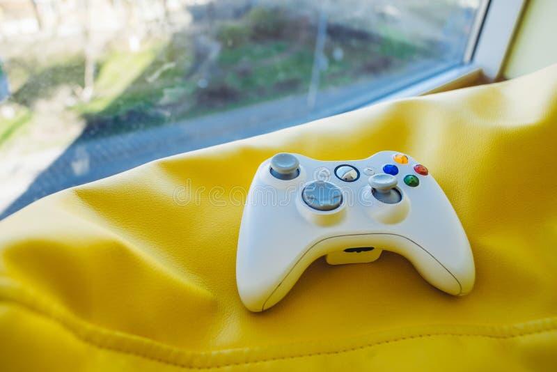 Palanca de mando blanca para la videoconsola en un fondo amarillo brillante cerca de la ventana fotografía de archivo