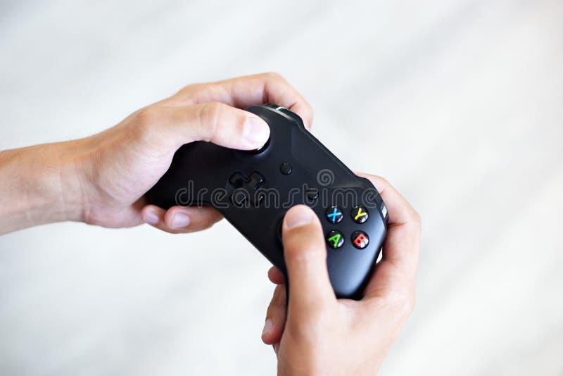 Palanca de mando negra en las manos aisladas en el fondo blanco El individuo est? jugando en la consola Competiti del juego de la foto de archivo