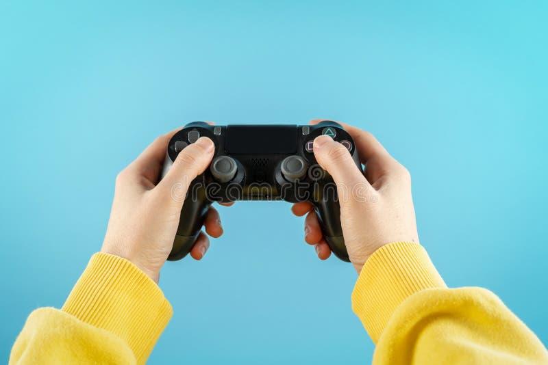 Palanca de mando negra en las manos aisladas en fondo azul en colores pastel fotografía de archivo