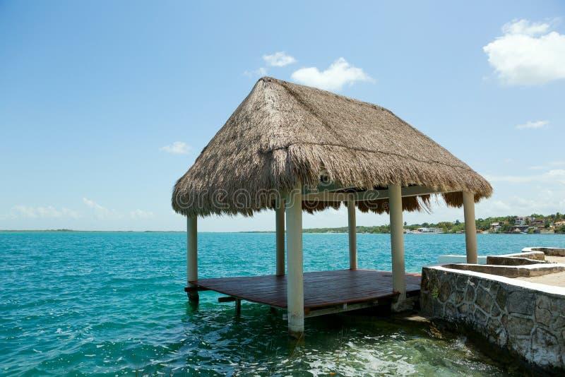 Palapa auf dem waterer im See Bacalar Mexiko lizenzfreies stockbild