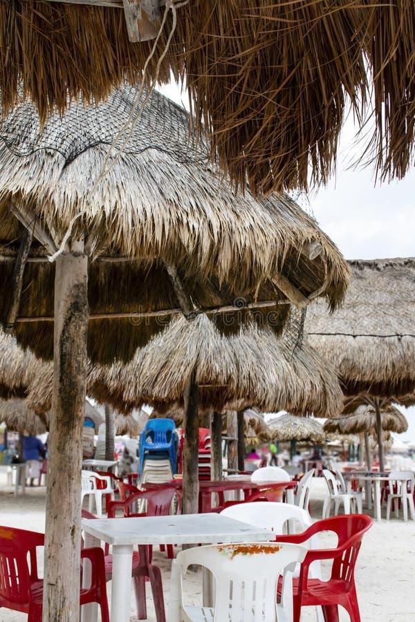 Palapa skuggor på stranden med plast-tabeller och stolar under dem - fokusera på förgrunden med suddig bakgrund med uniden royaltyfria bilder