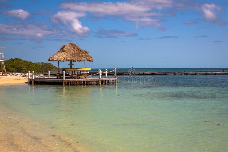 Palapas en la playa en la isla de Belice imagen de archivo