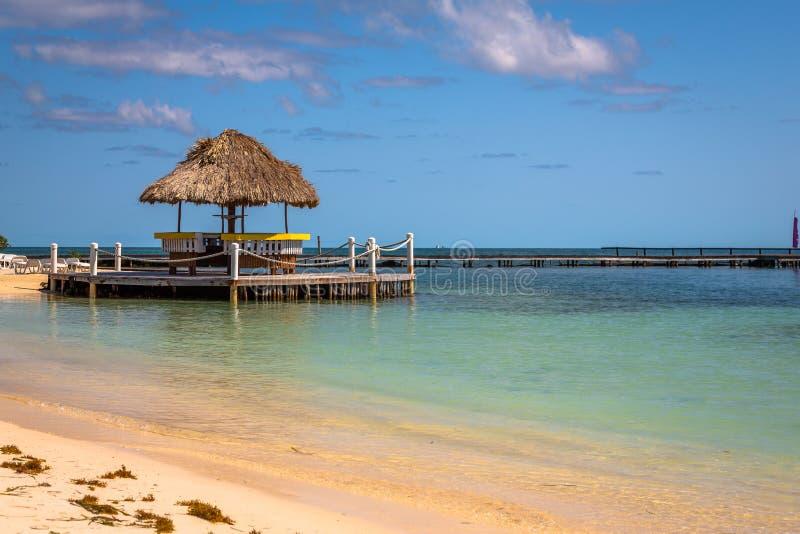 Palapas en la playa en la isla de Belice fotografía de archivo