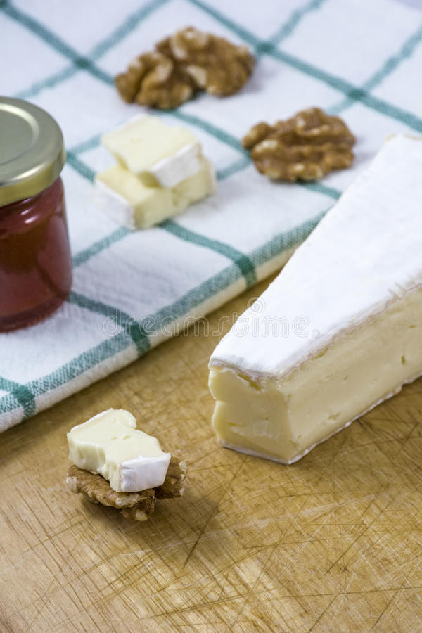 Palatable brie cheese with nuts, jam on the white towel with stripes royalty free stock photography