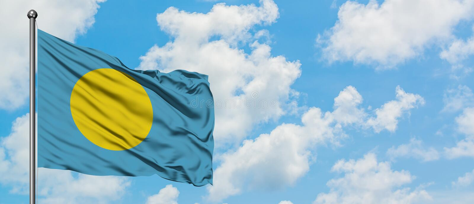 Palau flag waving in the wind against white cloudy blue sky. Diplomacy concept, international relations.  royalty free stock photography