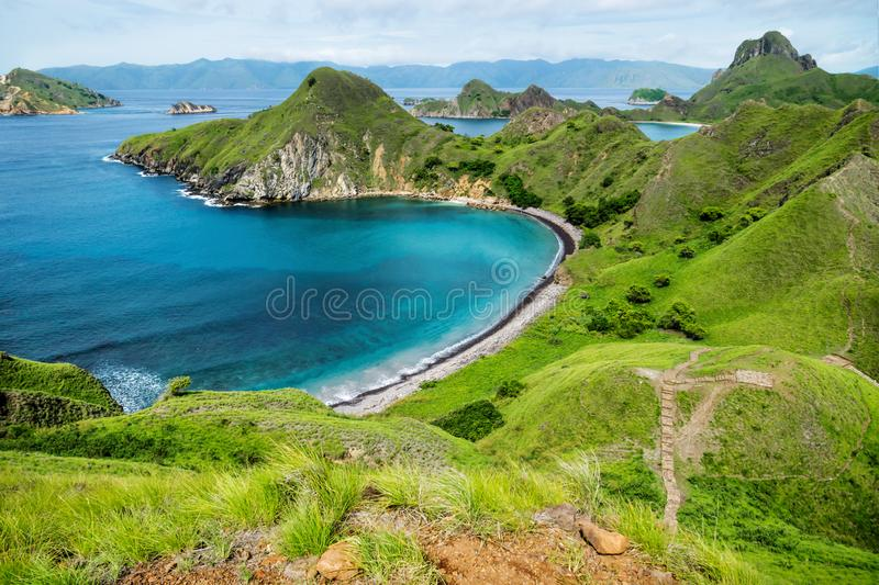 Palau Padar with ohm shaped beach in Komodo National Park, Flores, Indonesia. Palau Padar with ohm shaped beach with green hills in Komodo National Park, Flores royalty free stock photography