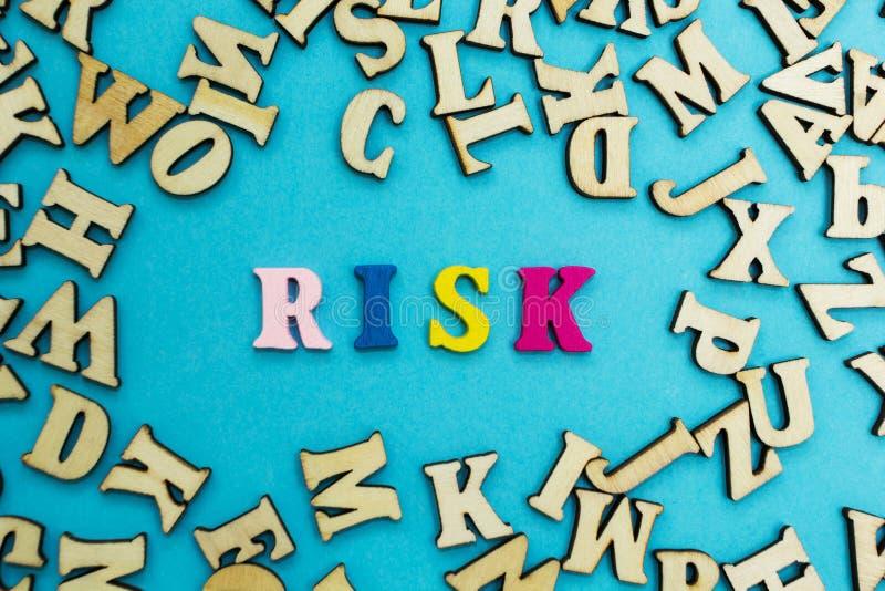 A palavra 'risco 'é apresentada das letras coloridos em um fundo azul Letras de madeira dispersadas foto de stock