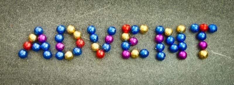 A palavra 'advento' sobre o chão, de balas de chocolate brilhando em ouro, azul e vermelho foto de stock