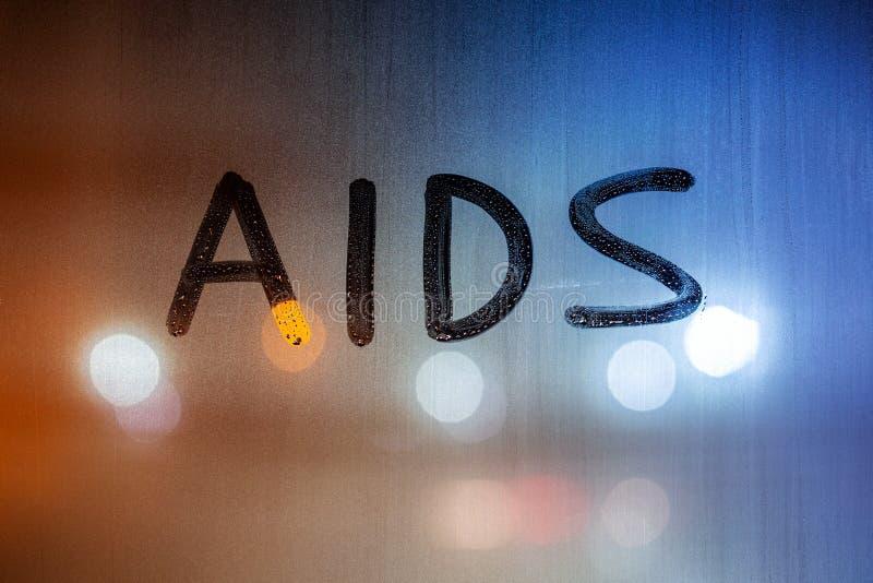 A palavra AIDS escrita no fecho de vidros molhados noturnos com fundo bokeh fotos de stock