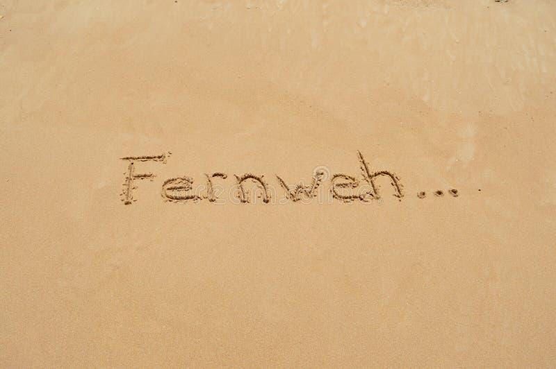 Palavra alemão 'Fernweh' na areia imagens de stock royalty free