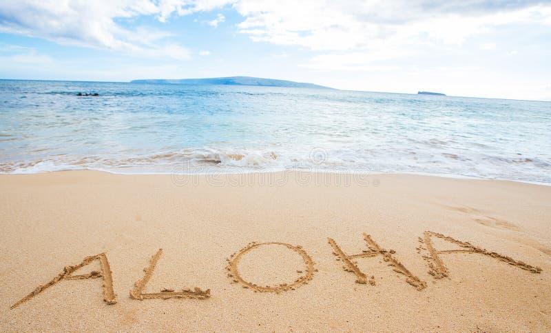 A palavra Aloha escrita na areia na praia fotos de stock