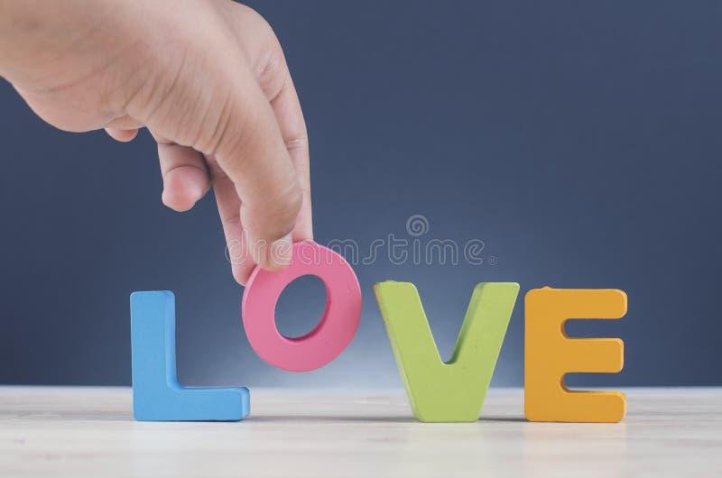 Palavra colorida AMOR das letras principais na mesa de madeira para o dia de Valentim fotografia de stock royalty free