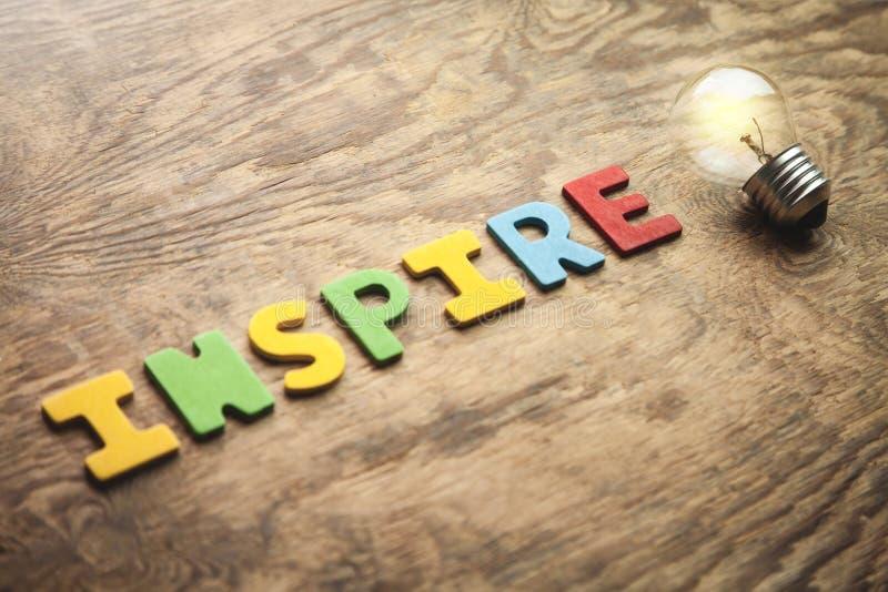 A palavra colorida inspira e ampola na tabela de madeira Inspiratio fotografia de stock