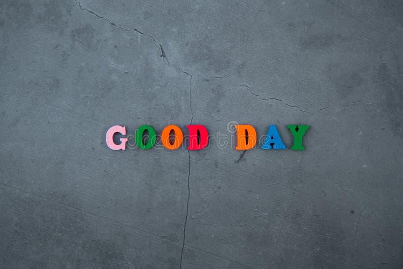 A palavra colorido do bom dia é feita de letras de madeira em um fundo emplastrado cinzento da parede foto de stock royalty free