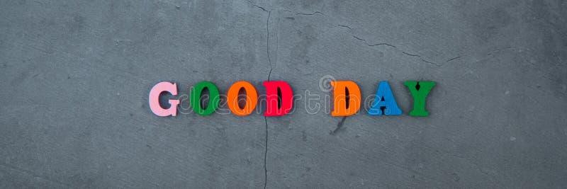 A palavra colorido do bom dia é feita de letras de madeira em um fundo emplastrado cinzento da parede imagem de stock