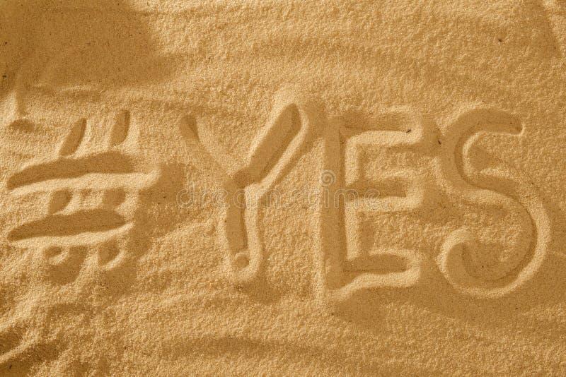 Palavra com hashtag sim na areia contra o sol do mar símbolo do conceito do feriado foto de stock royalty free
