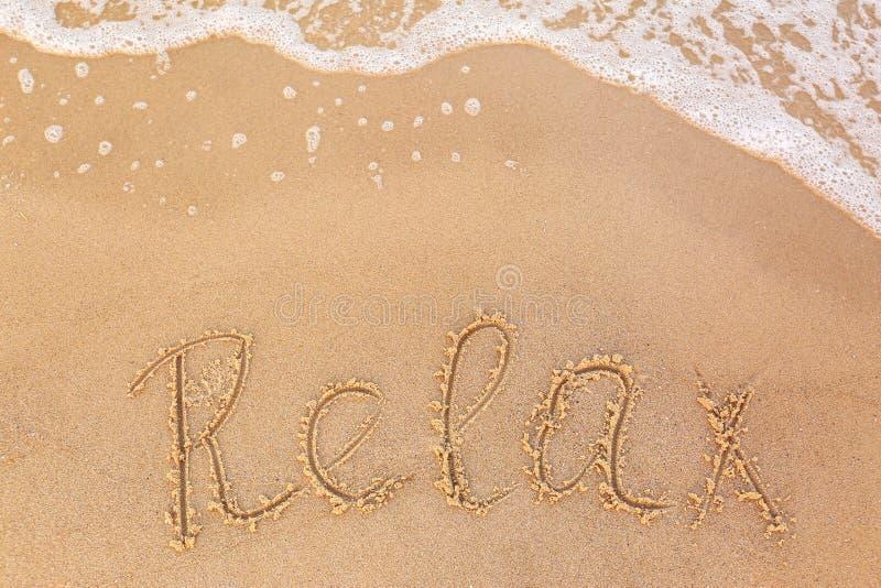 A palavra da palavra 'RELAXA 'escrito na onda do Sandy Beach e do mar, parte superior fotografia de stock