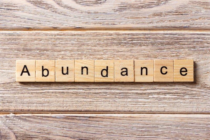 Palavra da abundância escrita no bloco de madeira texto na tabela, conceito da abundância imagem de stock