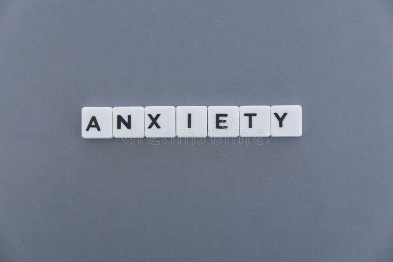 Palavra da ansiedade feita da palavra quadrada da letra no fundo cinzento foto de stock royalty free