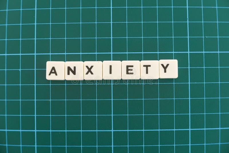 Palavra da ansiedade feita da palavra quadrada da letra no fundo quadrado verde da esteira imagens de stock
