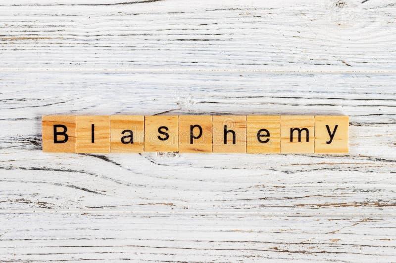 Palavra da BLASFÊMIA feita com conceito de madeira dos blocos imagens de stock