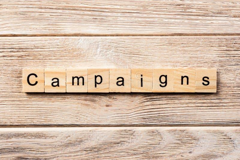 Palavra da campanha escrita no bloco de madeira texto na tabela, conceito da campanha foto de stock