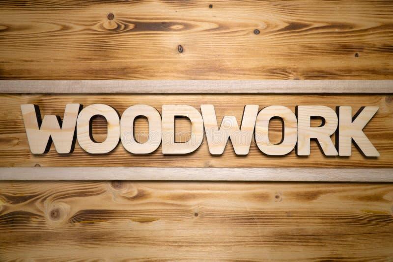 Palavra da CARPINTARIA feita com blocos de apartamentos na placa de madeira imagem de stock royalty free
