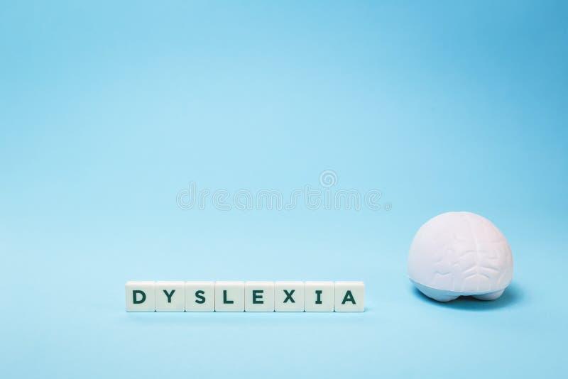Palavra da dislexia com um cérebro no azul com espaço da cópia fotografia de stock