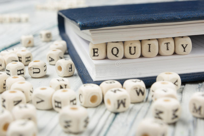 Palavra da EQUIDADE escrita no bloco de madeira ABC de madeira fotografia de stock