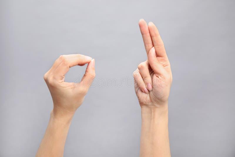 Palavra da exibição da mulher aprovada no fundo cinzento Linguagem gestual foto de stock