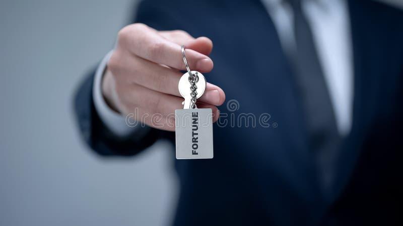 Palavra da fortuna no keychain na mão do homem de negócios, segredo chave do futuro bem sucedido imagens de stock royalty free
