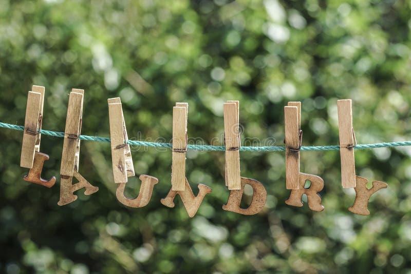 Palavra da LAVANDERIA escrita por letras de madeira penduradas na corda no jardim imagens de stock