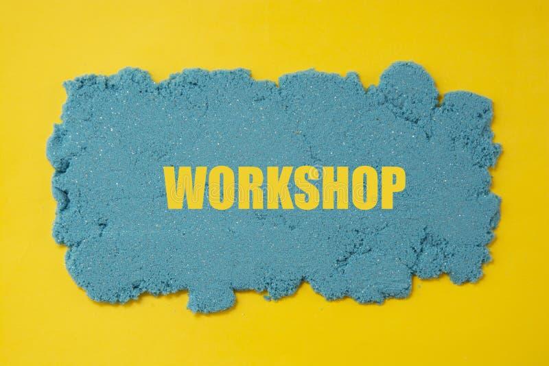 Palavra da oficina escrita no fundo amarelo com a areia cinética azul Conceito do negócio ilustração do vetor