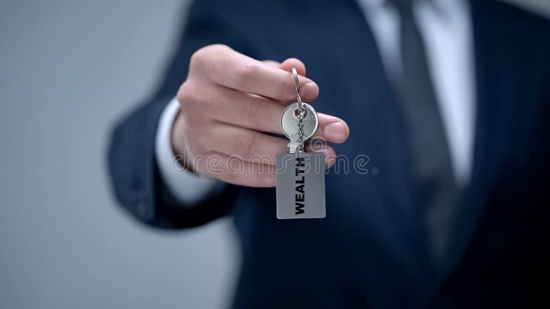 Palavra da riqueza no keychain na mão do homem de negócios, pontas chaves à vida rica bem sucedida fotografia de stock