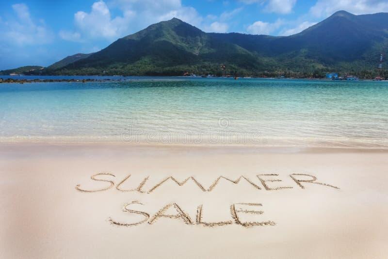 A palavra da venda do verão escrita na areia da praia fotos de stock royalty free