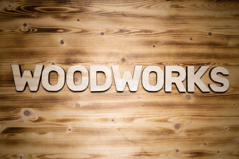 A palavra das carpintarias fez de letras de bloco de madeira na placa de madeira foto de stock royalty free