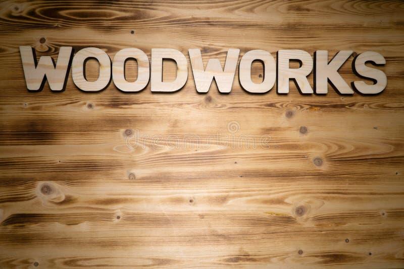A palavra das CARPINTARIAS fez de letras de madeira na placa de madeira imagem de stock royalty free