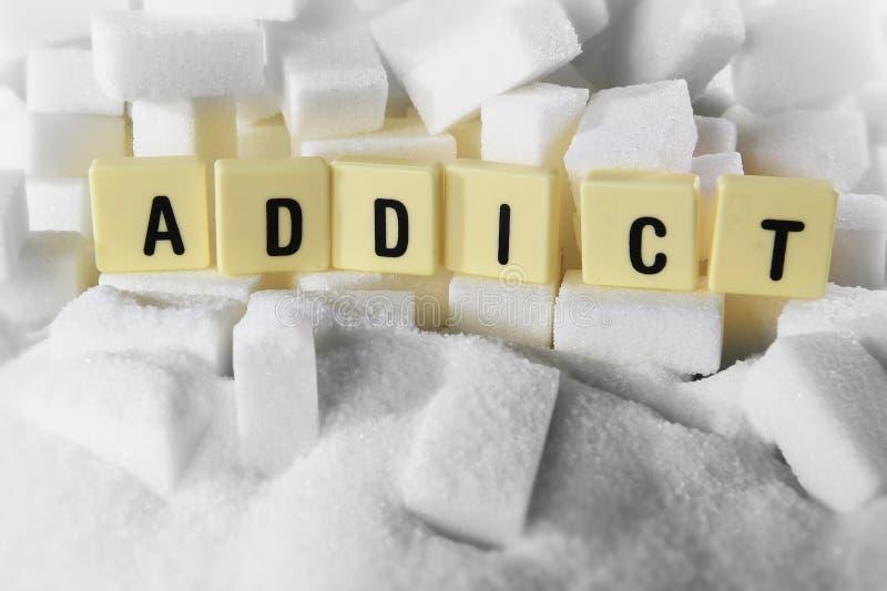 A palavra das letras de bloco do viciado na pilha de cubos do açúcar fecha-se acima no conceito do apego do açúcar imagem de stock
