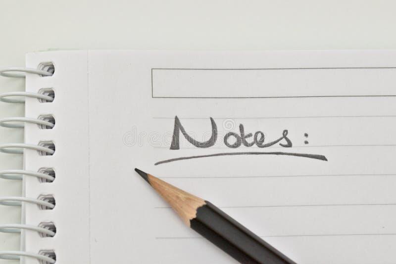 Palavra das notas e uma pena imagens de stock