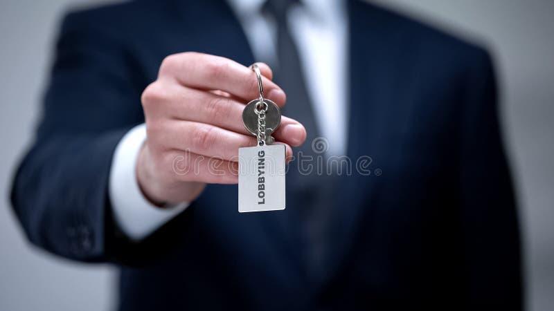 Palavra de incitação no keychain na mão do homem de negócios, proteção ilegal dos interesses fotos de stock royalty free