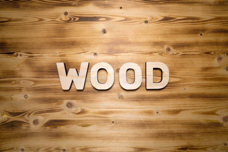 Palavra DE MADEIRA feita com blocos de apartamentos na placa de madeira imagem de stock royalty free