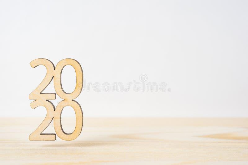 Palavra de madeira 2020 na tabela e no fundo branco foto de stock