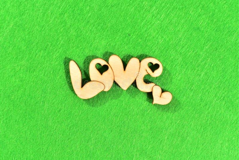 Palavra de madeira natural 'amor 'no fundo verde como a grama imagem de stock