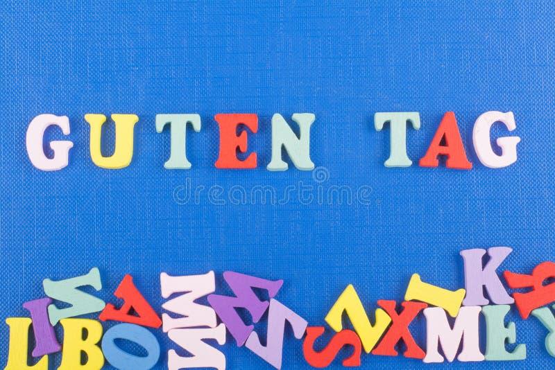 Palavra do BOM DIA da ETIQUETA de GUTEN no fundo azul composto das letras de madeira do bloco colorido do alfabeto do ABC, espaço imagem de stock