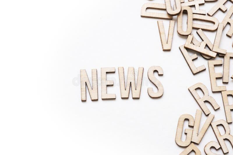 A palavra do conceito da notícia soletrou para fora no fundo branco fotos de stock