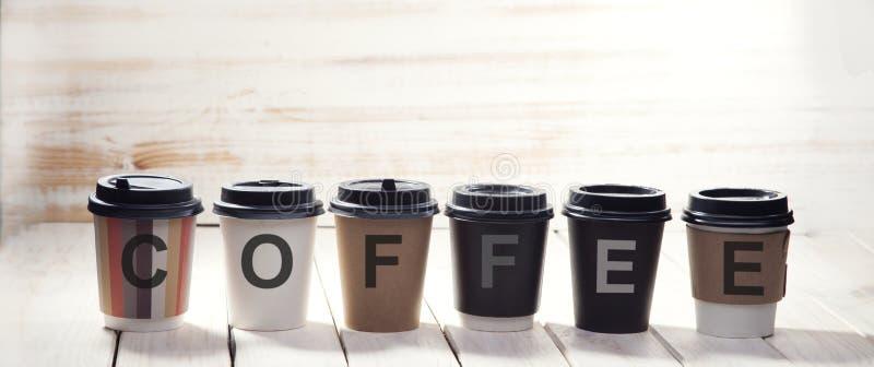 Palavra do copo de papel do café sobre na tabela de madeira foto de stock royalty free