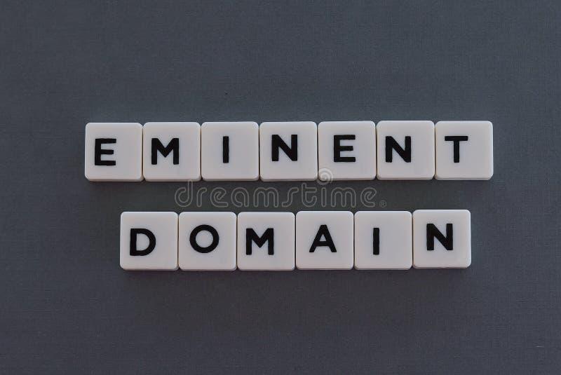 Palavra do domínio eminente feita da palavra quadrada da letra no fundo cinzento foto de stock royalty free