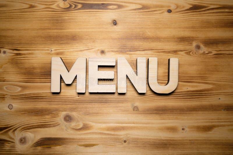 Palavra do MENU feita com blocos de apartamentos na placa de madeira fotografia de stock