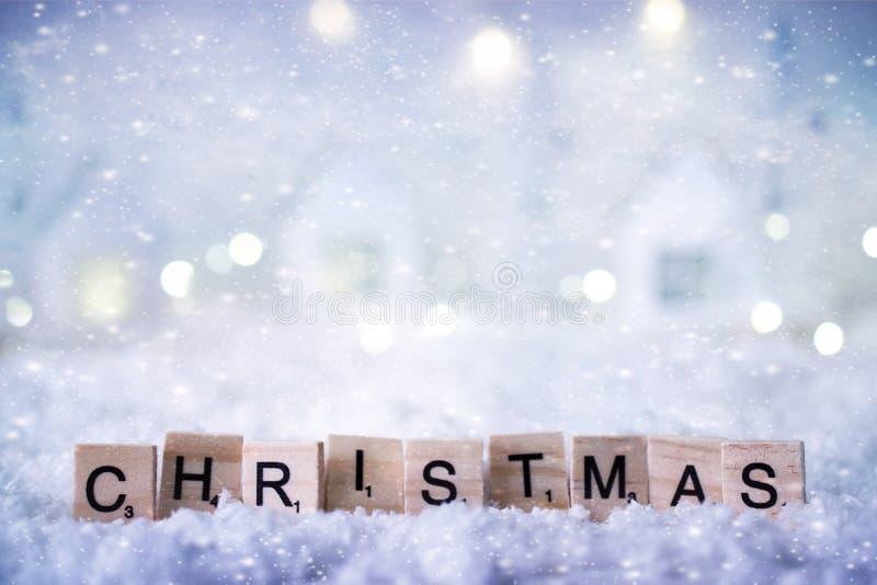 Palavra do Natal das letras no fundo do inverno com neve e luzes Molde, cartão Foco macio seletivo imagens de stock
